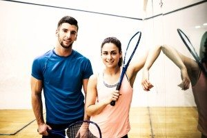 Man and woman holding squash rackets at squash court located in Unioville Athletic Club and Gym.
